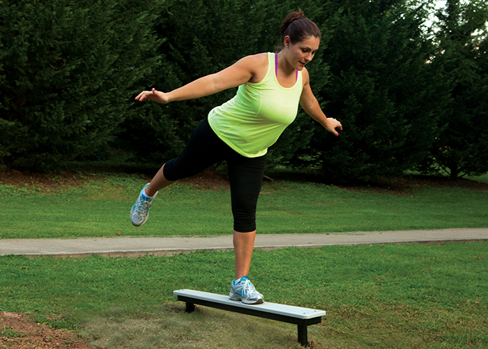 Woman working out on a Balance Plank at an Outdoor Fitness Park