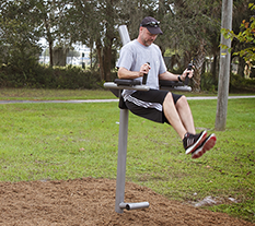 Man exercising in a Captain's Chair at an Outdoor Fitness Park