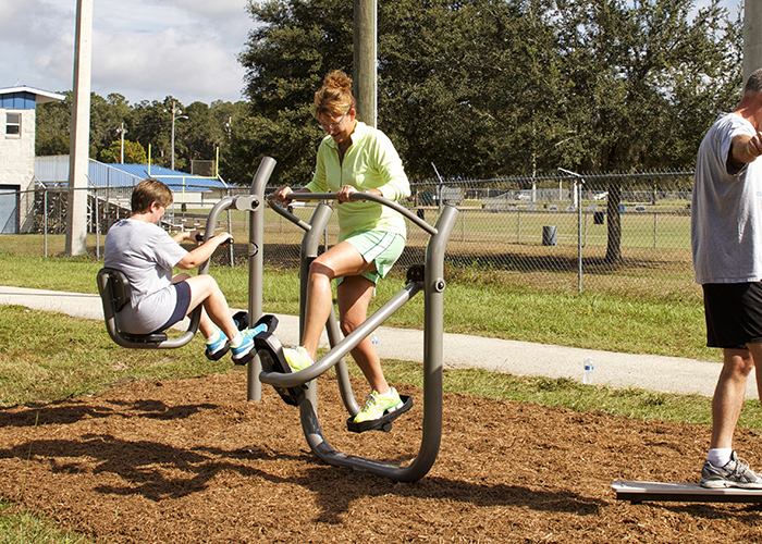 Woman working out on a Cardio Walker at an Outdoor Fitness Park