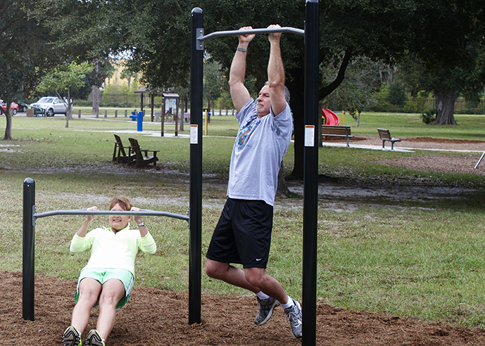 Man and Woman working out on Chin Up bars at an Outdoor Fitness Park