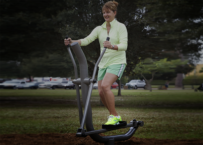 Woman exercising on an Elliptical machine at an Outdoor Fitness Park