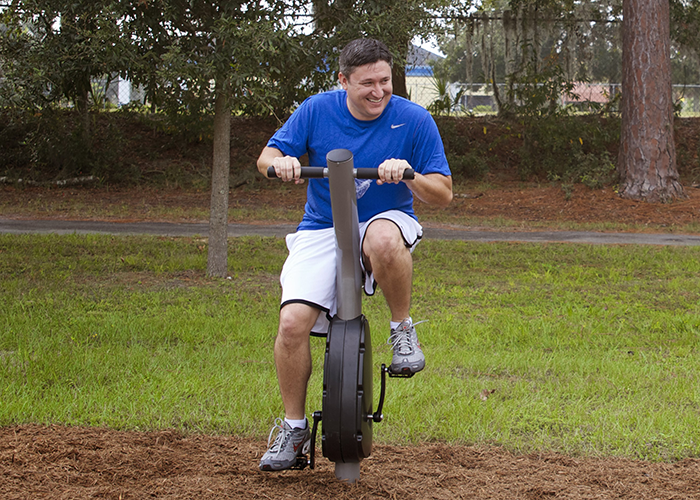 Man Exercising on an Upright Cycle in an Outdoor Fitness Park