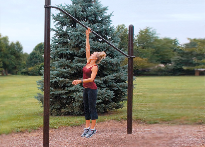 Woman working out with a High Jump at an Outdoor Fitness Park