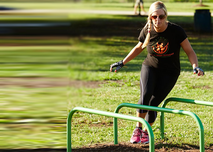 A Woman exercising with Hurdles at an Outdoor Fitness Park