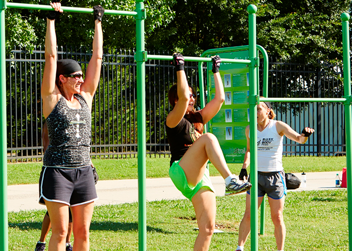Three Women Exercising on a Joint Use Pull-Up Bar at an Outdoor Fitness Park