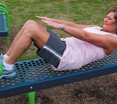 Woman doing a sit-up on Fitness Park sit-Up machine